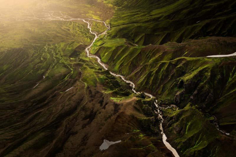 阳光照耀在冰岛绿色高地的一个山谷上。