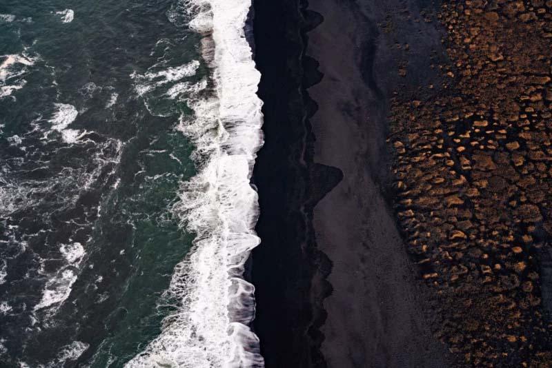 来自冰岛大海的白色浪花。与黑色沙滩形成了鲜明的对比。